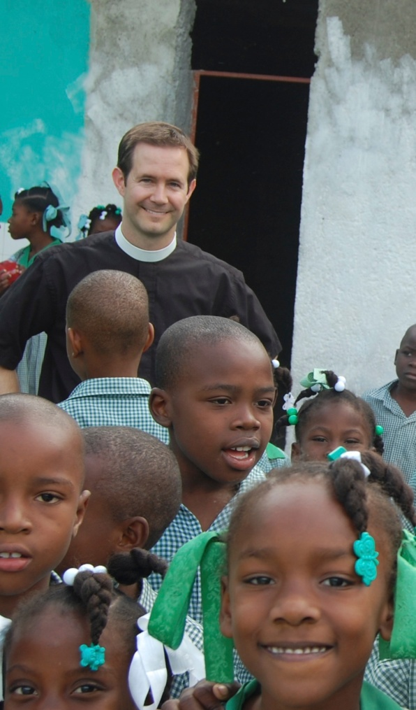 Me with kids in front of the new building of classrooms, not yet painted. You can see how the chalk erasers were cleaned against the wall.