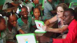 EFL Haiti team advisor introducing the OLPC machines to 5th grade students and Evens, an English teacher at the school.